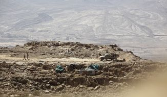 In this Friday, Feb. 2, 2018, photograph, two Yemeni soldiers allied to the country's internationally recognized government walk on a mountainside exposed to territory controlled by the Yemen's Shiite Houthi rebels below on the outskirts of Sanaa, Yemen. Yemen's conflict, which began as a civil war in 2014 and escalated into a regional proxy fight, drags on today. Winning the hardscrabble terrain takes time and costs dearly, only exacerbating the country's humanitarian crises and making a war that's seen over 10,000 people killed last that much longer. (AP Photo/Jon Gambrell)