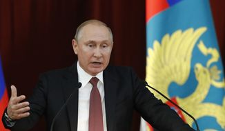"Russian Vladimir Putin gestures during a meeting with Russian ambassadors to foreign countries in Moscow, Russia, Thursday, July 19, 2018. Putin says his first summit with U.S. President Donald Trump was ""successful"" and is accusing Trump's opponents in the U.S. of hampering any progress on the issues they discussed. (Sergei Karpukhin/Pool Photo via AP)"