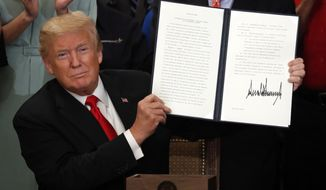 President Donald Trump holds up an Executive Order he signed that establishes a National Council for the American Worker, during a ceremony in the East Room of the White House in Washington, Thursday, July 19, 2018. (AP Photo/Pablo Martinez Monsivais)