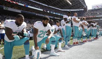In this Sept. 11, 2017, file photo, from left, Miami Dolphins' Jelani Jenkins, Arian Foster, Michael Thomas, and Kenny Stills, kneel during the singing of the national anthem before an NFL football game against the Seattle Seahawks in Seattle. (AP Photo/Stephen Brashear, File)