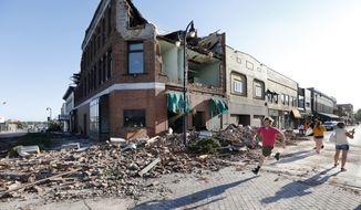 A local resident runs past a tornado-damaged building on Main Street, Thursday, July 19, 2018, in Marshalltown, Iowa. Several buildings were damaged by a tornado in the main business district in town including the historic courthouse. (AP Photo/Charlie Neibergall)