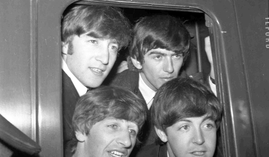 In this March 2, 1964 file photo, Britain's pop group The Beatles, from top left John Lennon, George Harrison and from bottom left, Ringo Starr and Paul McCartney pose in the window of train at Paddington Station in London. (AP Photo/Bob Dear, File)