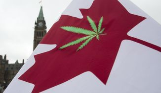 In this April 20, 2015 file photo, a Canadian flag with a cannabis leaf flies on Parliament Hill during a 4/20 event in Ottawa, Ontario. (Adrian Wyld/The Canadian Press via AP, File)