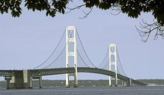 FILE - In this July 19, 2002 file photo, the Mackinac Bridge that spans the Straits of Mackinac is shown from Mackinaw City, Mich. A draft of a report released Thursday, July 19, 2018, commissioned by the state of Michigan outlining a worst-case scenario oil spill from a pipeline in the Straits of Mackinac calculates clean-up, restoration and liability costs at almost $2 billion. (AP Photo/Carlos Osorio, File)
