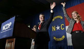 In this Nov. 9, 2016, file photo, North Carolina Democratic candidate for governor Roy Cooper and his wife Kristin greet supporters during an election night rally in Raleigh, N.C. In closely divided North Carolina, an intense power struggle between Republican lawmakers and Cooper will spill over to voting booths this fall. (AP Photo/Gerry Broome, File)