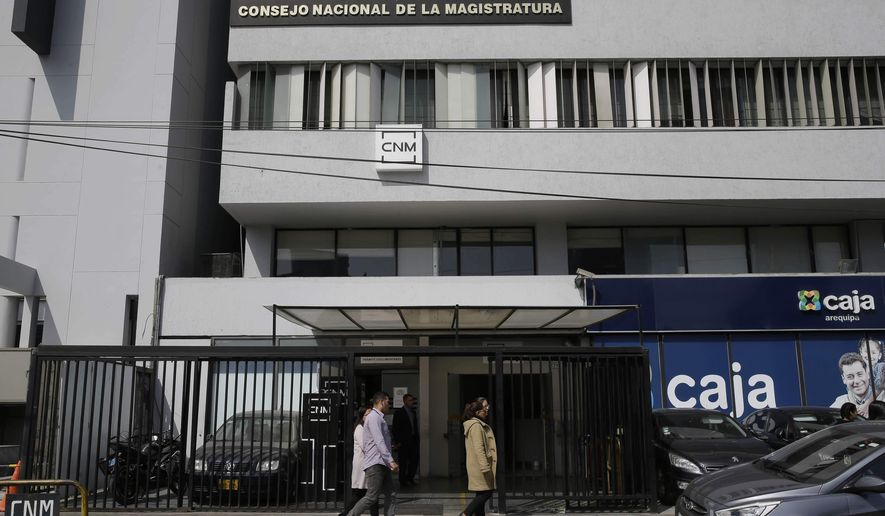 People pass Peru's National Judicial Council headquarters in Lima, Peru, Thursday, July 19, 2018. The head of Peru's judicial branch, Duberli Rodriguez, is offering his resignation over the latest corruption scandal to rock the South American nation, involving secretly recorded audio files released by a Peruvian website showing numerous judges willing to tender favors for friends. (AP Photo/Martin Mejia)