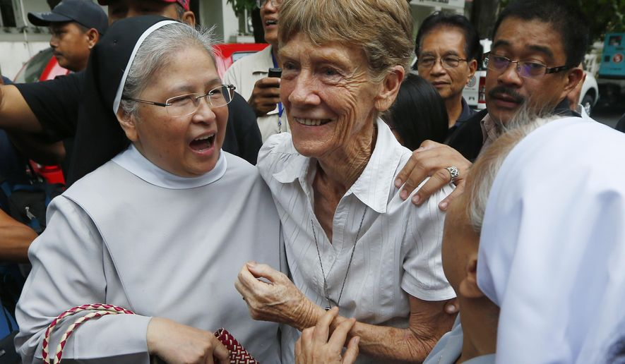 """FILE - In this Friday, May 25, 2018, file photo, Australian Roman Catholic nun Sr. Patricia Fox, center, is greeted by fellow nuns as she arrives to file her at the Justice Department shortly after filing a petition seeking to review a Bureau of Immigration order revoking her missionary visa in Manila, Philippines. The Philippine immigration bureau has ordered the deportation of Sr. Patricia Fox who has angered the president by joining anti-government rallies but her lawyers call the move """"persecution"""" and say they'll appeal. (AP Photo/Bullit Marquez, File)"""