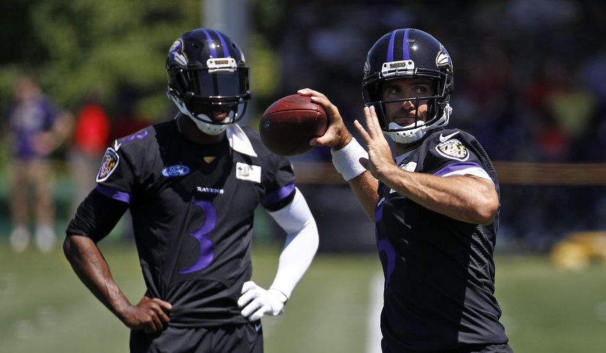 Baltimore Ravens quarterback Joe Flacco, right, throws a pass in front of quarterback Robert Griffin III during an NFL football training camp practice at the team's headquarters in Owings Mills, Md., Thursday, July 19, 2018. (AP Photo/Patrick Semansky)