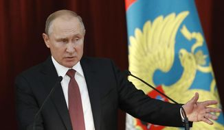"""Russian Vladimir Putin gestures during a meeting with Russian ambassadors to foreign countries in Moscow, Russia, Thursday, July 19, 2018. Putin says his first summit with U.S. President Donald Trump was """"successful"""" and is accusing Trump's opponents in the U.S. of hampering any progress on the issues they discussed. (Sergei Karpukhin/Pool Photo via AP)"""