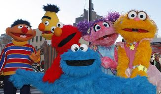 FILE - In this Feb. 10, 2010, file photo, characters from Sesame Street Live appear on the street by Madison Square Garden to celebrate the 30th anniversary of the live touring stage shows based on the PBS television series. in New York. From left are Ernie, Bert, Elmo, Cookie Monster (foreground), Abby Cadabby, and Zoe. The Sesame Street company is taking its beloved, critically-acclaimed brand of educational television into the highly profitable world of classroom curriculum. It's a move that experts say could open the door for other companies to sink their teeth into a sacred learning space. Sesame Workshop and McGraw-Hill Education announced their new partnership Thursday, July 19, 2018. (AP Photo/Kathy Willens, File)
