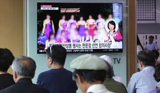 """A TV screen shows a blurred photo of North Korean restaurant workers in China, during a news program at the Seoul Railway Station in Seoul, South Kore, Friday, July 20, 2018. North Korea said that an August reunion of Korean families separated by war may not happen if South Korea doesn't immediately return some of its citizens who arrived in the South in recent years. The signs read: """"The two Koreas agreed to hold a reunion of Korean families."""" (AP Photo/Ahn Young-joon)"""