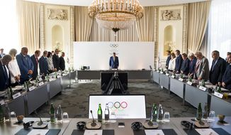 International Olympic Committee, IOC, President Thomas Bach from Germany, and the other board members stand for a minute in silence to honour the 100th anniversary of Nelson Mandela's birthday prior to the opening of the International Olympic Committee, IOC, executive board meeting, in Lausanne, Switzerland, Wednesday, July 18, 2018. (Jean-Christophe Bott/Keystone via AP)