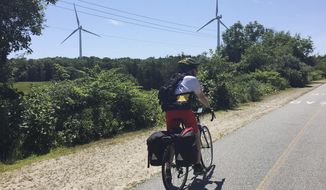 In this Friday, July 13, 2018 photo provided by Lori Riley, Associated Press reporter Pat Eaton-Robb rides past windmills on the Phoenix Trail in Fairhaven, Mass. The trail is part of the East Coast Greenway, a planned 3,000-mile collection of trails from Maine to Florida which is about 41 percent complete in southern New England. (Lori Riley via AP)