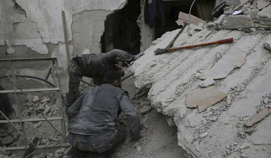 In this file photo released on Wednesday Feb. 21, 2018, which provided by the Syrian Civil Defense group known as the White Helmets, shows a member of the Syrian Civil Defense group searching for victims under the rubble of a destroyed house that attacked by Syrian government forces airstrike, in Ghouta, a suburb of Damascus, Syria. U.S. officials say the United States is finalizing plans to evacuate several hundred Syrian civil defense workers and their families from southwest Syria as Russian-backed government forces close in on the area. U.S., Britain and Canada are spearheading the evacuation that would transport members of the White Helmets group to transit camps in neighboring countries. From there, they will be sent to countries in Europe and possibly Canada. (Syrian Civil Defense White Helmets via AP)