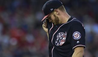 Washington Nationals starting pitcher Stephen Strasburg wipes his face between throws during the fifth inning of a baseball game against the Atlanta Braves at Nationals Park in Washington, Friday, July 20, 2018. (AP Photo/Susan Walsh)