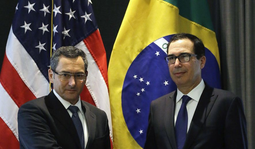 US Treasury Secretary Steven Mnuchin, right, shake hands with Brazil's Finance Minister Eduardo Guardia during a meeting in Sao Paulo, Brazil, Friday, July 20, 2018. (AP Photo/Nelson Antoine)