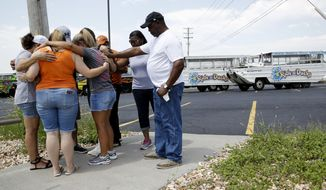 People pray outside Ride the Ducks, an amphibious tour operator involved in a boating accident on Table Rock Lake, Friday, July 20, 2018 in Branson, Mo. (AP Photo/Charlie Riedel)