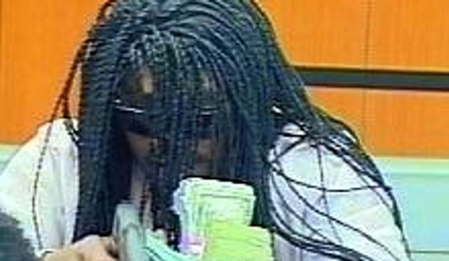 An image from video provided by the Durham Police Department shows a suspect in the robbery of a bank Wednesday, July 18, 2018, in Durham, N.C.  Police say the robber shot and wounded a teller before getting away with money. (Durham Police Department via AP)