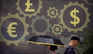 People walk past a mural displaying world currency symbols on the outside of a bank in Beijing, Friday, July 20, 2018. China's central bank is allowing its tightly controlled yuan to drift lower against the dollar, a move that could help exporters cope with U.S. tariff hikes but raises the risk of reigniting an outflow of capital Beijing spent months trying to stanch. (AP Photo/Mark Schiefelbein)