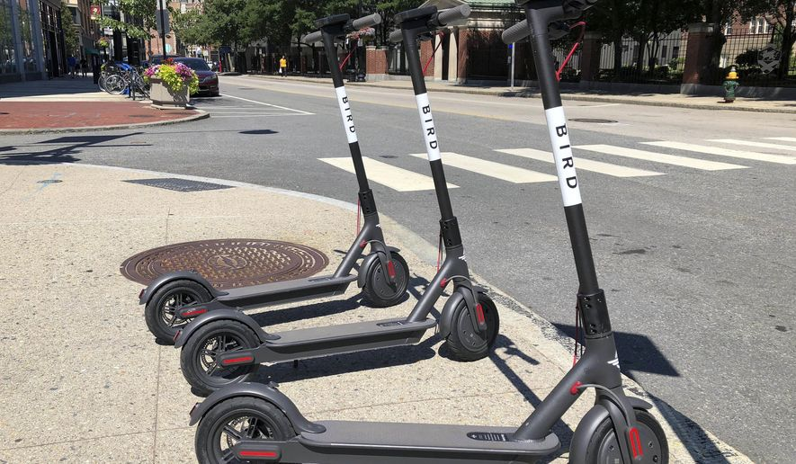 Three dockless scooters stand on a sidewalk across the street from a Johnson & Wales University campus, Friday, July 20, 2018, in downtown Providence, R.I. A California company left its electric rental scooters on city sidewalks in Providence, and in Cambridge and Somerville, Mass., Friday without warning. (AP Photo/ Jennifer McDermott)