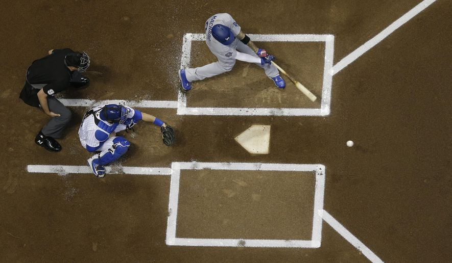 Los Angeles Dodgers' Manny Machado hits a single during the first inning of a baseball game against the Milwaukee Brewers Friday, July 20, 2018, in Milwaukee. (AP Photo/Morry Gash)
