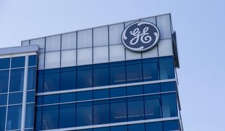 FILE- In this Jan. 16, 2018, photo, the General Electric logo is displayed at the top of their Global Operations Center in the Banks development of downtown Cincinnati. General Electric Co. reports earnings Friday, July 20. (AP Photo/John Minchillo, File)