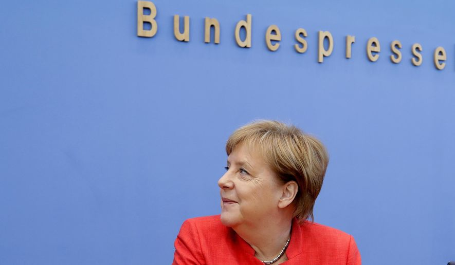 German Chancellor Angela Merkel smiles at the beginning of her annual summer press conference at the Bundespressekonferenz in Berlin, Germany, Friday, July 20, 2018. (AP Photo/Ferdinand Ostrop)