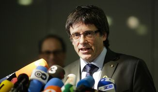 FILE - In this May 15, 2018 file photo former Catalan leader, Carles Puigdemont, addresses the media during a news conference in Berlin, Germany. A Spanish Supreme Court judge has dropped his extradition requests for six Catalan separatist politicians wanted on rebellion charges.  (AP Photo/Markus Schreiber, file)