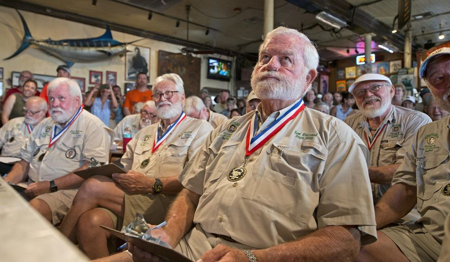 In this photo provided by the Florida Keys News Bureau, former winners of the Hemingway Look-Alike contest, including Tom Grizzard, third from right, evaluate entrants Thursday, July 19, 2018, at Sloppy Joe's Bar in Key West, Fla. The competition, that has attracted about 150 entrants, is part of the island city's annual Hemingway Days Festival that pays homage to Ernest Hemingway who lived and wrote in Key West in the 1930s. (Andy Newman/Florida Keys News Bureau via AP)