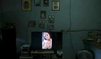 This July 18, 2018 photo shows a photo of Adalicia Montecinos and her son Johan Bueso Castillo displayed on a television screen inside their home in La Libertad, Honduras. The last time Montecinos saw her son, he had two tiny teeth. Now he has a mouthful. The Honduran boy took his first steps, spoke his first words and had his first birthday in U.S. government custody. (AP Photo/Esteban Felix)