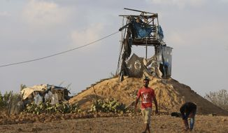 Palestinians inspect a military observation post that was hit by an Israeli tank shell east of Khan Younis, southern Gaza Strip, Friday, July 20, 2018. Israel pummeled Hamas targets in Gaza killing four Palestinians on Friday in a series of air strikes after gunmen shot at soldiers near the border, officials said. The Gaza Health Ministry said four Palestinians were killed. The militant Islamic Hamas that rules Gaza said three of the dead were members of the group. (AP Photo/Adel Hana)