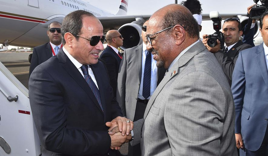 In this photo released by the Egyptian Presidency, Egyptian President Abdel-Fattah el-Sissi, left, is greeted by Sudanese President Omar al-Bashir on his arrival to  Khartoum, Sudan, Thursday, July 19, 2018. (Egyptian Presidency via AP)