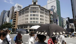 People walk under intense sun at Ginza shopping district in Tokyo Friday, July 20, 2018. A deadly heat wave in Japan has many residents in the Japanese capital questioning the wisdom of staging the Tokyo 2020 Olympics in July and August. (AP Photo/Eugene Hoshiko)