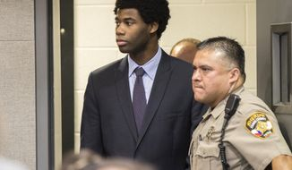 FILE - In this July 11, 2018, file photo, Meechaiel Criner, accused of killing University of Texas student Haruka Weiser in April 2016, is escorted into a courtroom in Austin, Texas. A jury on Friday, July 20, 2018, found Criner guilty of capital murder. Criner, a foster care runaway at the time of the slaying, received an automatic life sentence. He was ineligible for the death penalty because he was 17 when the crime occurred. (Ricardo Brazziell/Austin American-Statesman via AP, File)