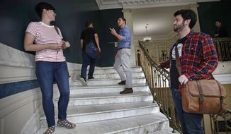 Zak Ringelstein, center, a Democratic candidate for U.S. Senate in Maine, talks with a passerby while climbing the stairs inside City Hall to attend a meeting of the Southern Maine Democratic Socialists of America in Portland, Maine, Monday, July 16, 2018. On the ground in dozens of states, there is new evidence that democratic socialism is taking hold as a significant force in Democratic politics. At right is Charles Tetelman, field director of Ringelstein's campaign. (AP Photo/Charles Krupa)