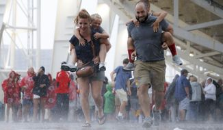 Spectators run through a downpour during a rain delay before a baseball game between the Cincinnati Reds and the Pittsburgh Pirates, Friday, July 20, 2018, in Cincinnati. (AP Photo/John Minchillo)