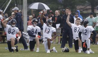 Chicago Bears players warm up during an NFL football training camp in Bourbonnais, Ill., Saturday, July 21, 2018. (AP Photo/Nam Y. Huh)