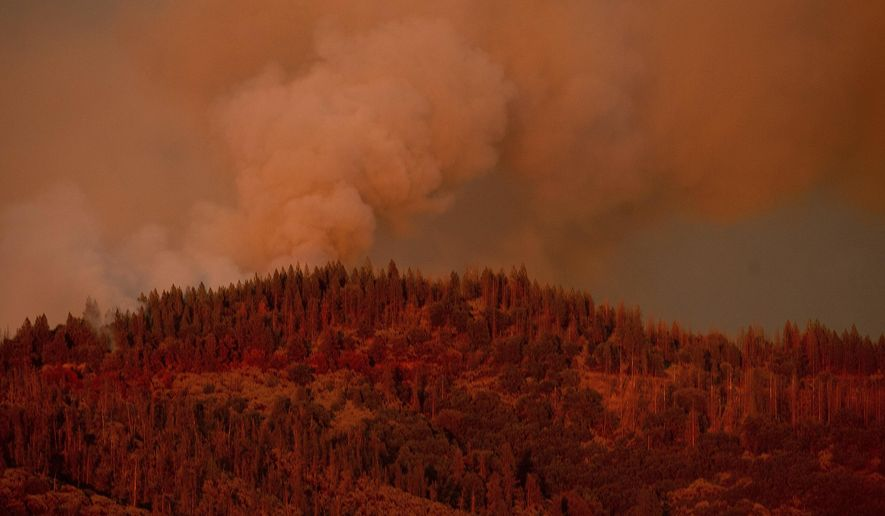 FILE - In this Monday, July 16, 2018, file photo, the Ferguson Fire burns along a ridgeline in unincorporated Mariposa County, Calif. Officials said Saturday, July 21, 2018, that the Ferguson fire is churning northward, sending up smoke that has been obscuring valley views in the park.  (AP Photo/Noah Berger, File)