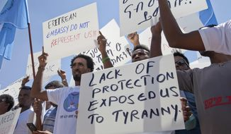 File - In this Monday, June 25, 2018, file photo, Eritrean asylum seekers hold a rally in front of Israeli Ministry of Foreign Affairs in Jerusalem. The startling and sudden thaw between longtime enemies Eritrea and Ethiopia is opening up a world of possibilities for the countries' residents: new economic and diplomatic ties, telephone and transport links and the end to one of the most bitter feuds between neighbors. But the fledgling peace is raising new questions for Eritrea's diaspora, tens of thousands of people who fled the Eritrean government's tight grip, a rigid compulsory military and endemic poverty who are cautiously waiting to see how the truce will shape their homeland and perhaps offer them a chance to return. (AP Photo/Caron Creighton, File)