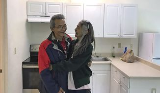 In this Friday, July 13, 2018 photo, Clyde Didrickson and his wife, Charlotte, smile and hug each other in their new home in Juneau, Alaska. The couple was able to get their new home through a Tlingit Haida Regional Housing Authority grant funding program aimed to help veterans. (Gregory Philson /The Juneau Empire via AP)