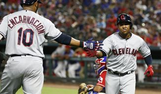Cleveland Indians' Jose Ramirez, right, celebrates his solo home run with Edwin Encarnacion (10) against the Texas Rangers during the sixth inning of a baseball game, Friday, July 20, 2018, in Arlington, Texas. (AP Photo/Jim Cowsert)