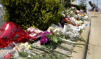 A woman looks at a memorial in front of Ride the Ducks Saturday, July 21, 2018 in Branson, Mo. One of the company's duck boats capsized Thursday night resulting in several deaths on Table Rock Lake. (AP Photo/Charlie Riedel)