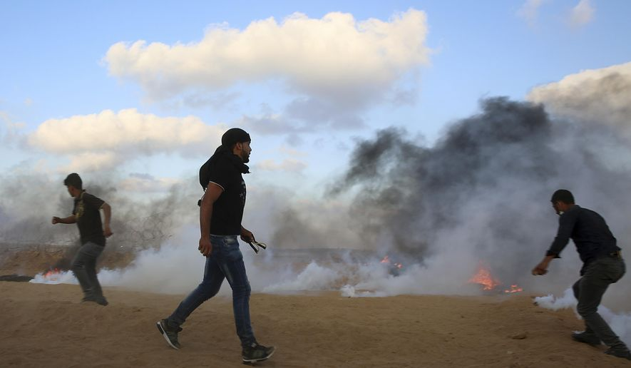 Protesters try to throw back teargas canisters fired by Israeli troops near the fence of the Gaza Strip border with Israel, during a protest east of Khan Younis, southern Gaza Strip, Friday, July 20, 2018. Israel targeted Hamas positions in Gaza, killing four Palestinians on Friday in a series of air strikes after gunmen shot at soldiers near the border, officials said. (AP Photo/Adel Hana)