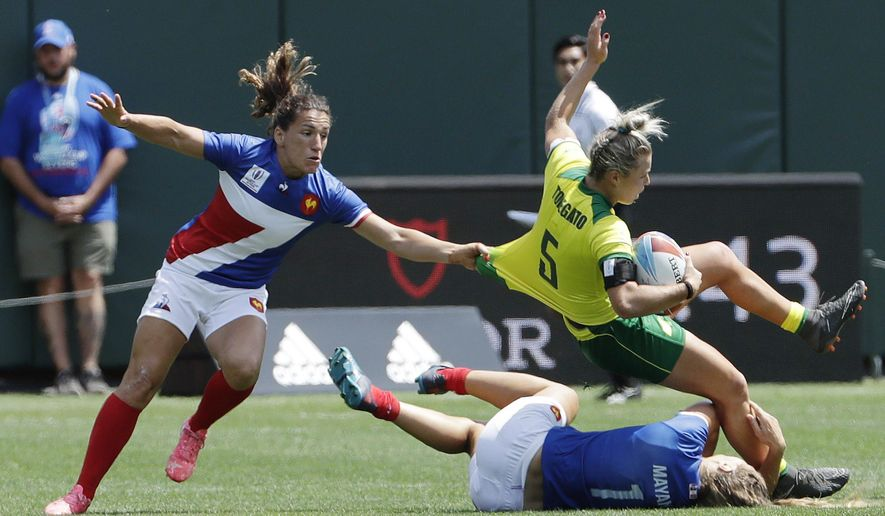 Australia's Emma Tonegato (5) is tackled by France's Marjorie Mayans (1) as a teammate closes in during a Women's Rugby Sevens World Cup semifinal in San Francisco, Saturday, July 21, 2018. (AP Photo/Jeff Chiu)