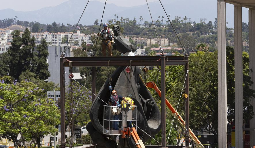 """Workers remove tooling from a steel frame cage used to hoist the Music Center Plaza's Jacques Lipchitz 10-ton bronze sculpture, """"Peace on Earth,"""" to its new home on the west side of Music Center Plaza downtown Los Angeles Saturday, July 21, 2018. (AP Photo/Damian Dovarganes)"""