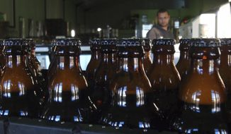 In this June 5, 2018, photo, bottles of freshly bottled beer stand in the Darling Brewery in Darling, South Africa. The South African brewery appears to be the first in Africa to go carbon-neutral as more businesses across the continent adjust to climate change, and as consumers become more careful about the products they buy. (AP Photo/Neil Shaw)