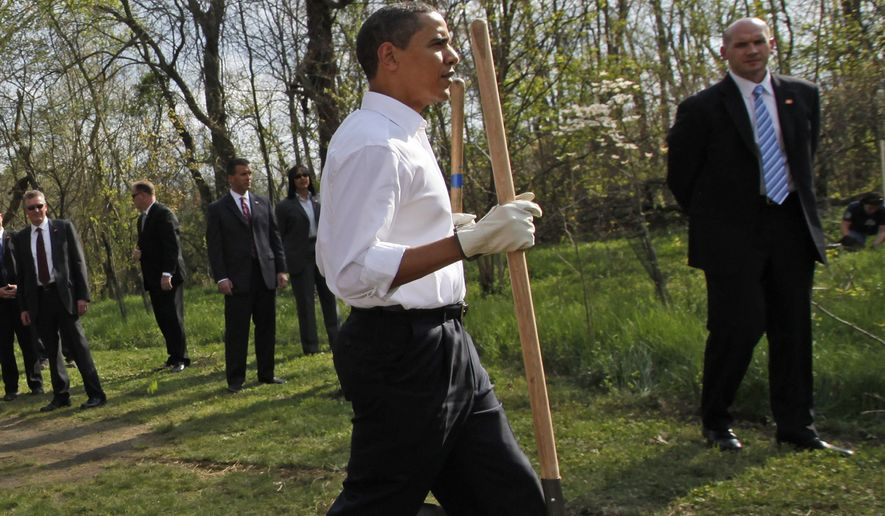 U.S. Secret Service agents stand watch as President Barack Obama walks with two shovels as he gets ready to plant a tree while participating in a national service project at Kenilworth Aquatic Garden in Washington, Tuesday, April 21, 2009. (AP Photo/Charles Dharapak)