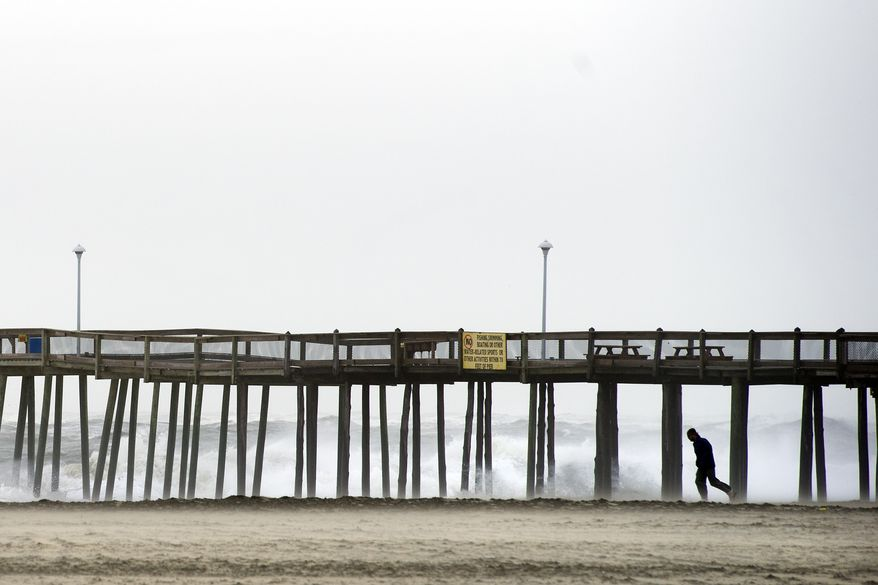 A man walks against a stiff wind under the Jolly Roger Amusement Pier in Ocean City, Md., Saturday, Oct. 3, 2015. Rainfall and heavy winds are expected to last through the weekend. (AP Photo/Cliff Owen) ** FILE **