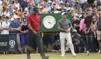 Tiger Woods of the US and Francesco Molinari of Italy, right, walk along a fairway during the final round of the British Open Golf Championship in Carnoustie, Scotland, Sunday July 22, 2018. (AP Photo/Peter Morrison)