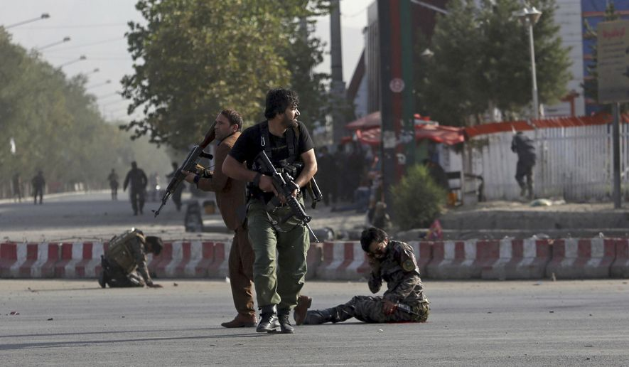Afghan security personnel stand guard next to wounded comrades at the site of an attack near the Kabul International Airport, in Kabul, Afghanistan, Sunday, July 22, 2018. An Afghan spokesman said there has been a large explosion near the Kabul airport shortly after the country's controversial first vice president landed on his return from abroad. Gen. Abdul Rashid Dostum and members of his entourage were unharmed in the explosion on Sunday, which took place as his convoy had already left the airport (AP Photo/Rahmat Gul)